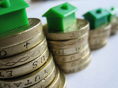 London buy to let market - pound coins with Monopoly houses on top