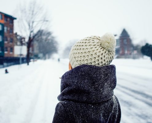 How to keep warm this winter- girl in winter coat and bobble hat looking at building