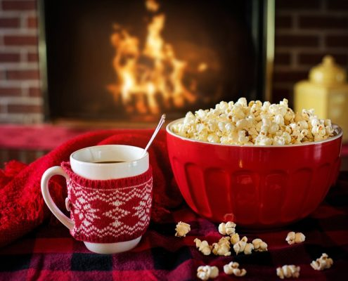 How to keep your home warm this winter - popcorn and coffee in front of open fire