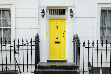 Exterior image of a property with a bright yellow door